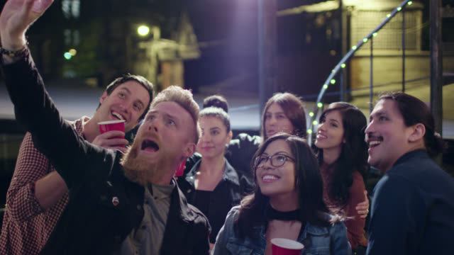 stockvideo's en b-roll-footage met ws slo mo. friends pose for a group selfie at rooftop party. - milleniumgeneratie