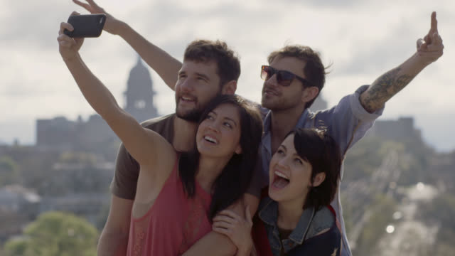 Friends pose for crazy selfie overlooking downtown Austin, Texas snd gather around smartphone to see