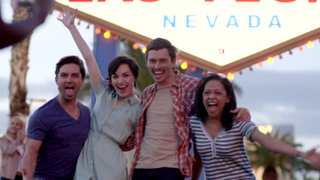 Friends pose for picture in front of Las Vegas sign