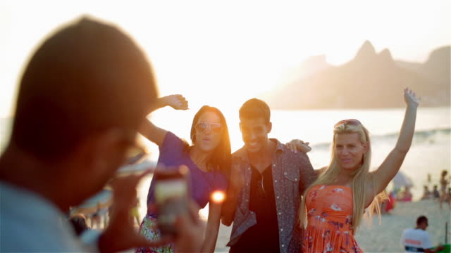Friends pose for smartphone photo on Ipanema Beach at sunset