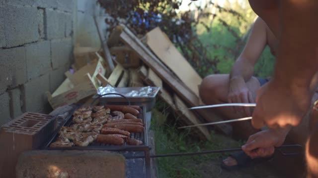 家の後ろの裏庭でバーベキューを準備する友人 - コイントス点の映像素材/bロール
