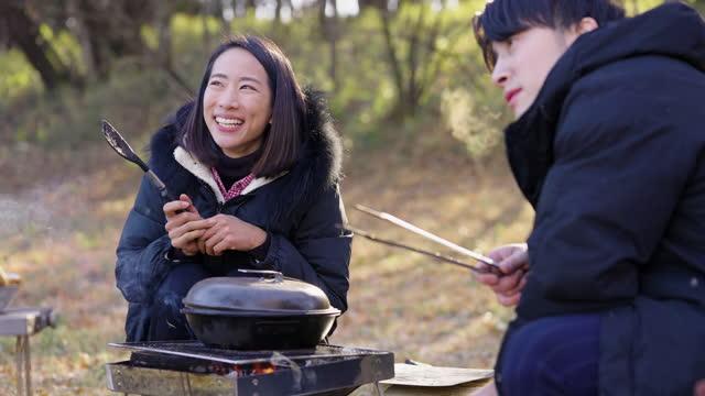 冬のキャンプ場で朝食を準備する友人 - キャンプする点の映像素材/bロール