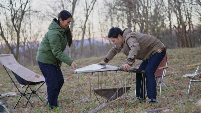 キャンプストーブを準備し、薪で火を作る友人 - キャンプする点の映像素材/bロール