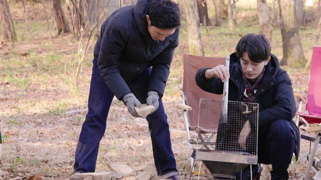 キャンプストーブを準備し、薪で火を作る友人 - ピクニック点の映像素材/bロール