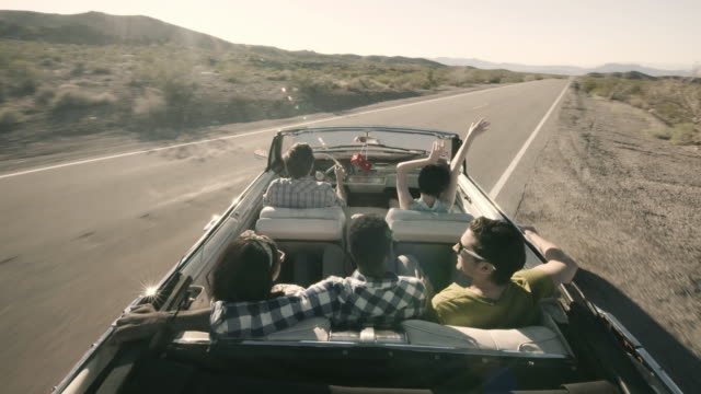 Friends pull on to lonely desert road and throw their hands in the air