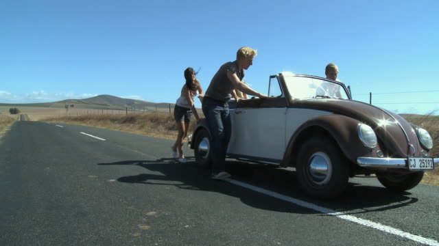 ws pan friends pushing car / cape town, south africa - schieben stock-videos und b-roll-filmmaterial