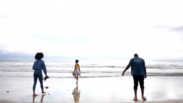 vidéos et rushes de ws friends putting toes in ocean during trip to beach - 25 29 ans