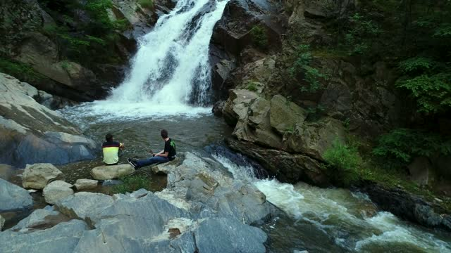 friends relaxing by the waterfall in wilderness drone stock video - spring flowing water stock-videos und b-roll-filmmaterial