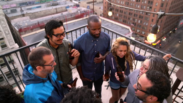 vídeos de stock e filmes b-roll de friends relaxing in the early evening sun drinking beer - afro americano