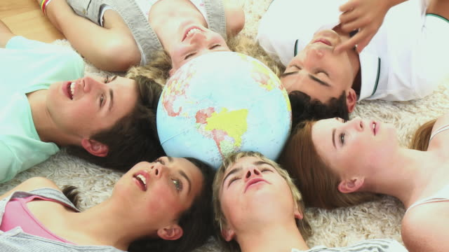 cu friends (girl 14-15) relaxing on floor with heads together in circle holding globe / cape town, south africa - mappamondo video stock e b–roll
