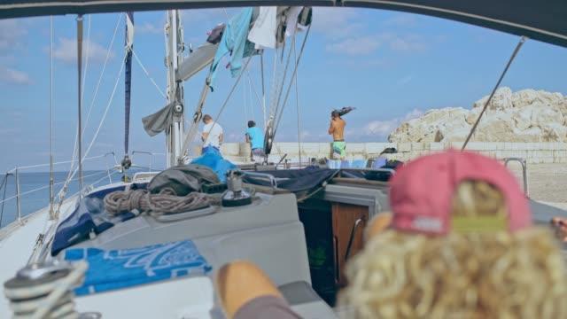 4k freunden entspannen sie sich auf segelboot und sonnigen pier, real-time - besatzung stock-videos und b-roll-filmmaterial