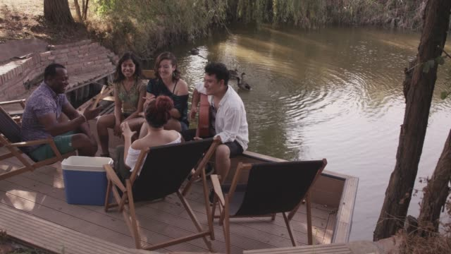 friends relaxing on the riverbank - riverbank stock videos & royalty-free footage
