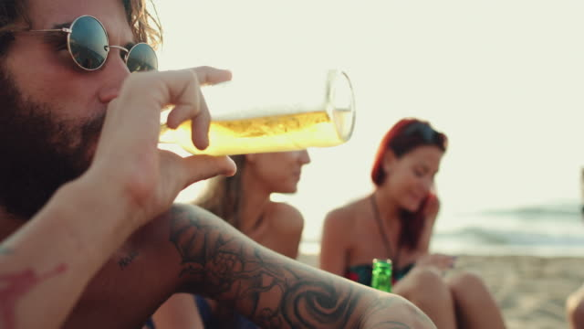 friends relaxing together on the beach at sunset - drinking beer stock videos and b-roll footage