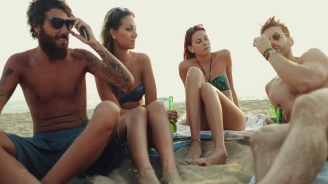 Friends relaxing together with sunglasses on the beach