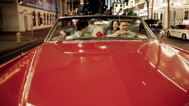 Friends ride triumphantly through downtown Las Vegas in classic convertible