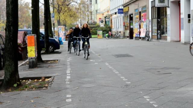 vídeos de stock e filmes b-roll de friends riding bicycles on sidewalk by buildings - estação do ano