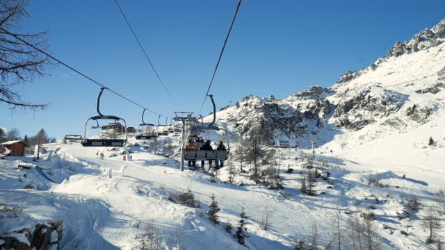 vidéos et rushes de friends riding chairlift up mountain in the alps - sitting