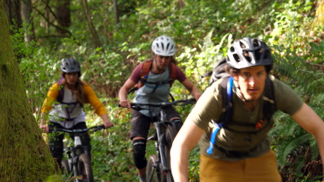ms friends riding mountain bikes together down trail in forest - sports helmet stock videos and b-roll footage