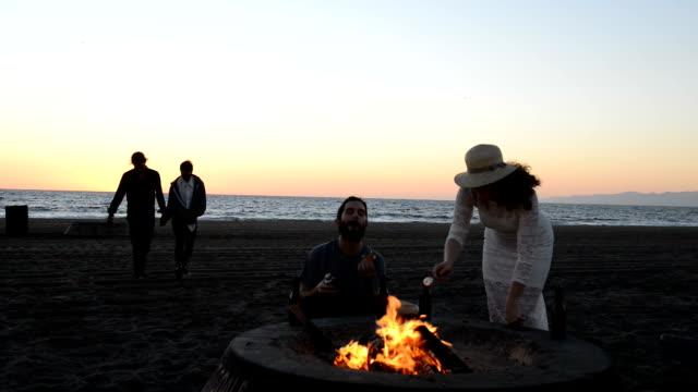 Friends Roast Marshmallows at Beach Bonfire