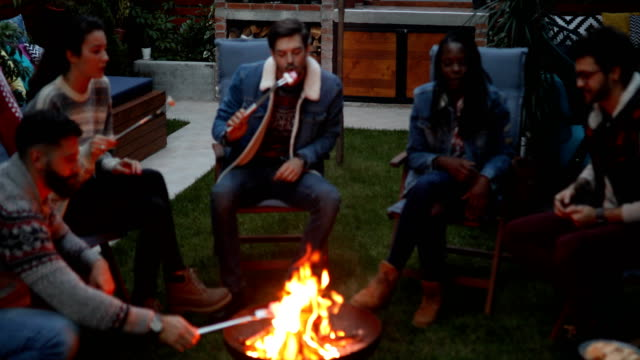 friends roasting marshmallows on fire pit - medium group of people stock videos & royalty-free footage