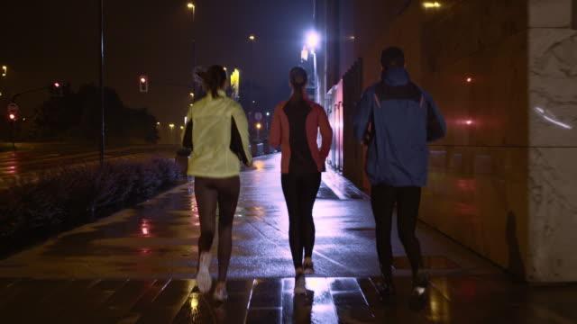 ts amici correre in città, in una notte piovosa - pink color video stock e b–roll