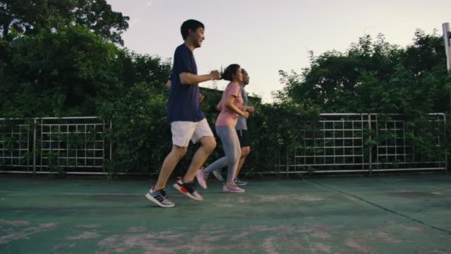 vidéos et rushes de amis courant le jogging ensemble dans le ciel de coucher du soleil public côté de fond de vue lent d'exercice d'exercice extérieur d'activité saine d'activité saine - grand groupe de personnes