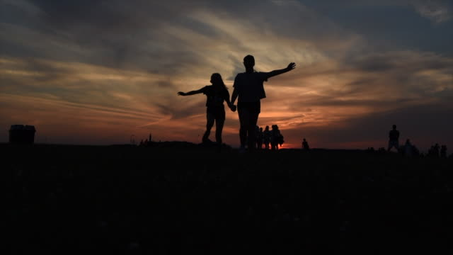 friends running toward the camera, silhouetted by the sunset - friendship stock videos & royalty-free footage