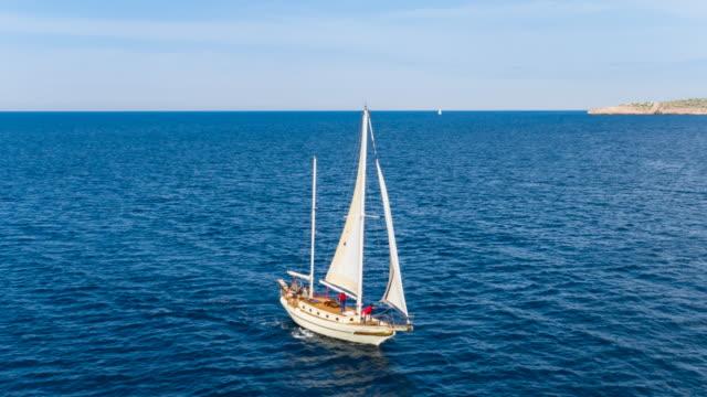 ha ws friends sailing in mediterranean sea on vintage wooden yacht - 帆点の映像素材/bロール