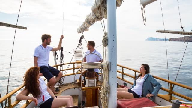 ms friends sailing in mediterranean sea on vintage wooden yacht - freizeitaktivität stock-videos und b-roll-filmmaterial