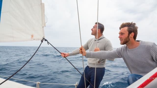 MS friends sailing in stormy mediterranean sea on modern yacht