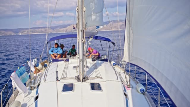 4K Friends sailing on sunny sailboat, real time