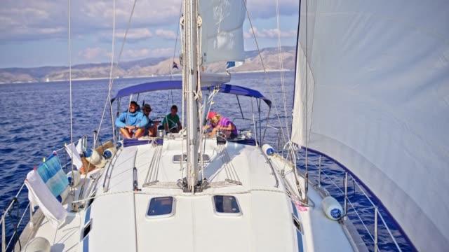 4k freunde segeln auf sonnigen segelboot, real-time - segelmannschaft stock-videos und b-roll-filmmaterial