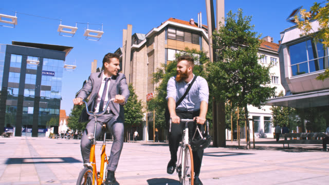 slo mo friends separate while riding with bicycles in the city - colleague stock videos & royalty-free footage