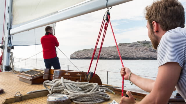 MS friends setting sail in mediterranean sea on classic wooden yacht