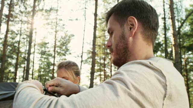 vídeos de stock e filmes b-roll de friends setting up tent - 20 24 anos
