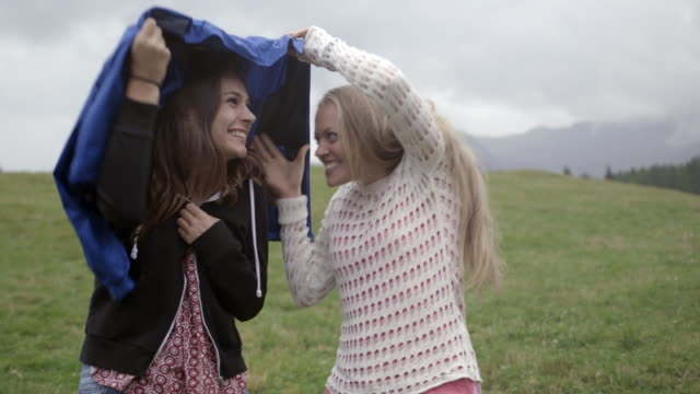 Friends sharing a raincoat
