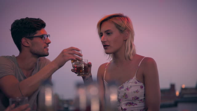 Friends sharing drink at a rooftop party