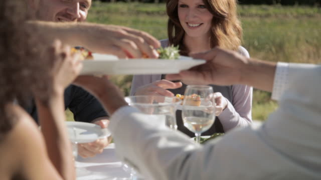 friends sharing food at outdoor dinner party - farm to table stock videos & royalty-free footage