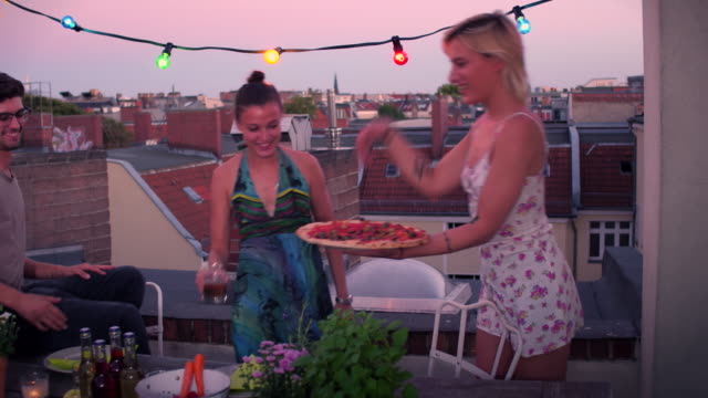 Friends sharing pizza on urban rooftop