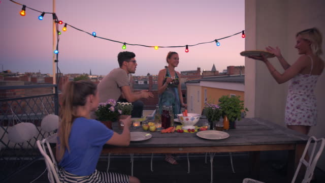 friends sharing pizza on urban rooftop - social gathering stock videos & royalty-free footage