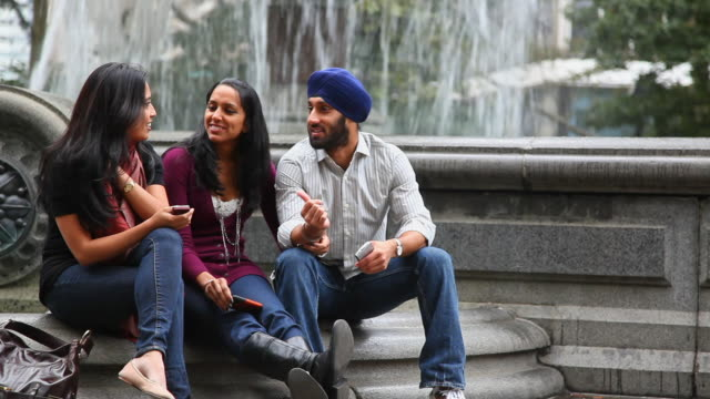 friends sitting and talking at fountain in park - turban stock videos & royalty-free footage