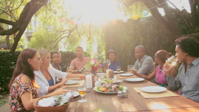 vidéos et rushes de friends sitting at a table in a garden - barbecue jardin