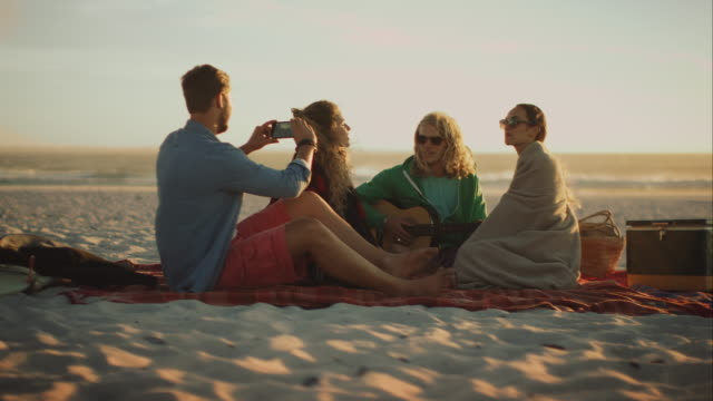 friends sitting at beach and relacing - photograph stock videos & royalty-free footage