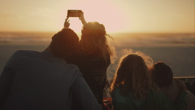 stockvideo's en b-roll-footage met vrienden zit op strand en relacing - friendship