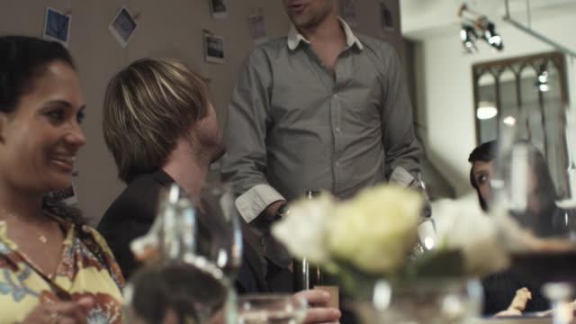 vídeos y material grabado en eventos de stock de slo mo pan ms r/f friends sitting by dining table and toasting wine at party / new york city, new york, usa - cena con amigos
