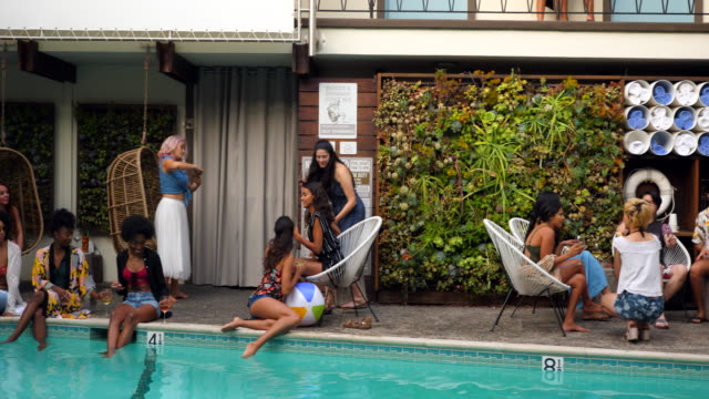 stockvideo's en b-roll-footage met pan friends sitting by hotel pool during party - poolparty