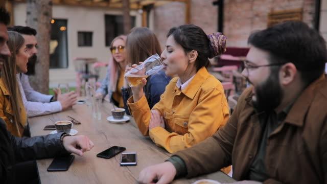 stockvideo's en b-roll-footage met vrienden zitten in sidewalk cafe - koffie drank