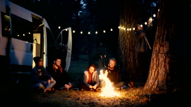 friends sitting near campfire in the forest near the camper van - tenda video stock e b–roll