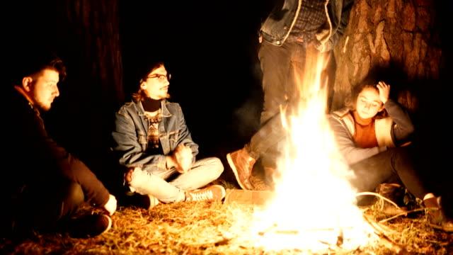 vídeos de stock e filmes b-roll de friends sitting near campfire in the forest near the camper van - fogueira de acampamento