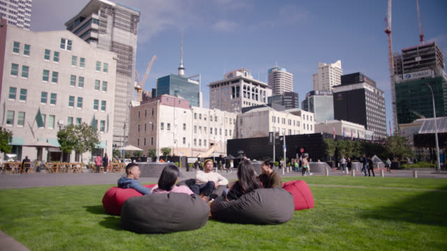 friends sitting on beanbags in public square - new zealand stock videos & royalty-free footage